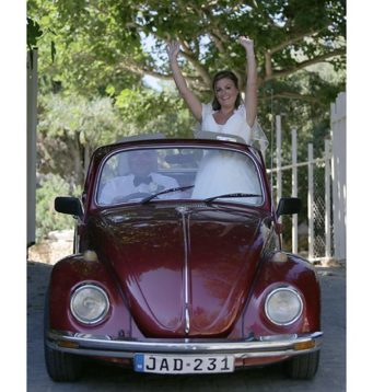 Bride standing up in a VW Beetle