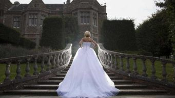Bride walking up the stairs of Fawsley Hall wedding venue
