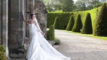 Bride standing outside the entrance to Fawsley Hall wedding venue