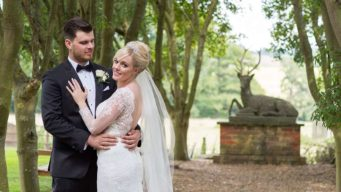 Bride & groom standing in the gardens at Fawsley Hall wedding venue