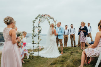 Cornish celebrant conducting a ceremony on a beach under a floral archway