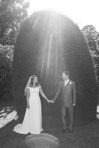 Bride and groom standing by a bush holding hands