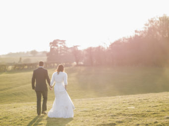 Bride and groom walking along a field in the sunshine
