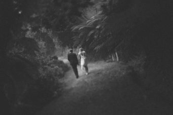 Bride and groom walking along a driveway in black and white