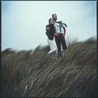 Bride and groom standing on a hill top, bride wearing her groom's jacket