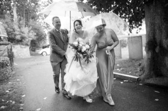Bride and her father walking to the church under an umbrella