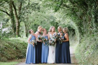 Bride and her bridesmaids in shades of blue, on the driveway at Pengenna Manor