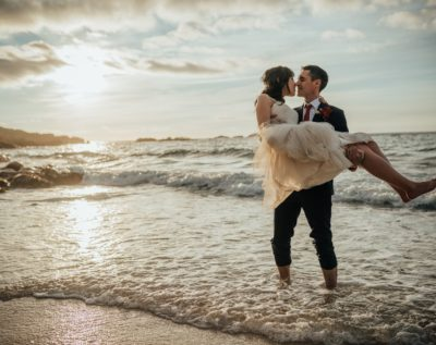 Bride being lifted up by her groom for a kiss while standing in the sea