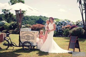 Bride standing by a ice cream tricycle at The Falmouth Hotel, perfect Cornwall wedding venue