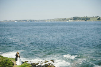 Bride and groom standing on rocks by the sea at The Falmouth Hotel