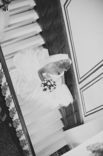 Bride walking down a sweeping staircase at The Falmouth Hotel, ideal Cornwall wedding venue