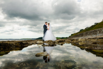 Bride and groom standing on rocks by the sea at The Falmouth Hotel, ideal Cornwall wedding venue