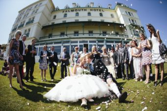 Bride and groom doing confetti outside The Falmouth Hotel exterior, ideal Cornwall wedding venue