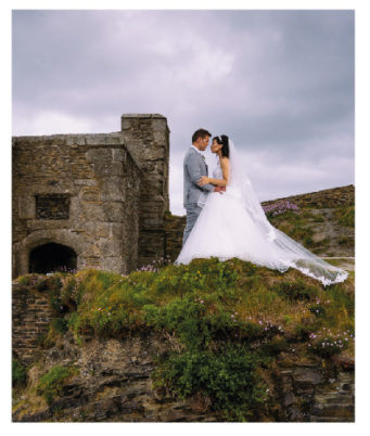 Bride and groom standing by an old fort at The Falmouth Hotel, ideal Cornwall wedding venue