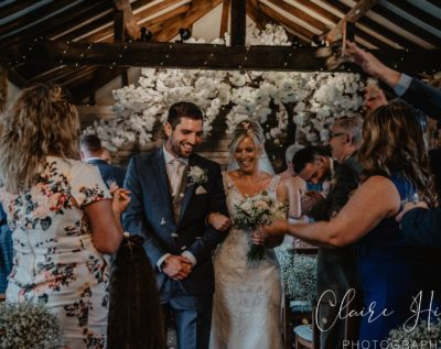 Bride and groom walking through a flower arch at Dodmoor House