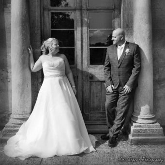 Bride and groom standing at the doors to Cranford Hall, perfect wedding venue in Kettering, Northamptonshire