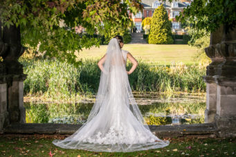 Bride standing at the lake at Dunchurch Park Hotel wedding venue