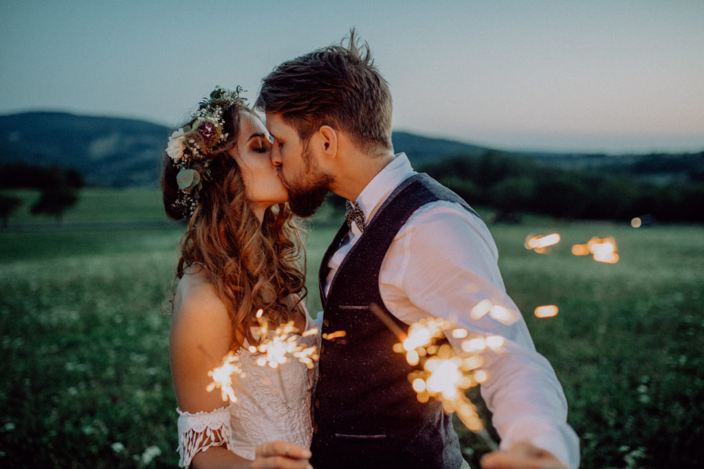 Wedding day schedule - bride and groom with sparklers at the end of the evening